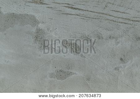 Rough flat wall plastered with concrete. Visible spots and stripes. Surface grey with pimples bumps and hollows. Smeared uneven on the wall.