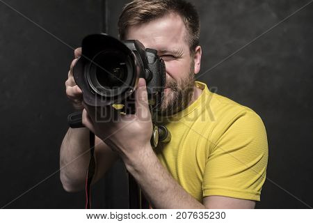 A pretty man - a photographer in a yellow T-shirt shoots in the studio on a DSLR camera which stands on a tripod. Close-up.