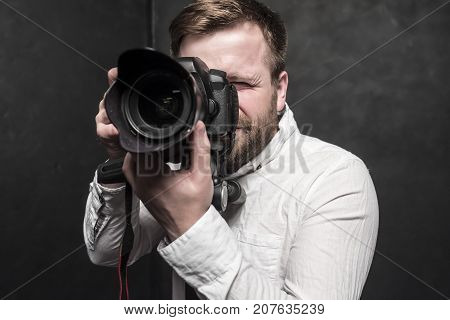 A pretty man - a photographer in a white shirt shoots in the studio on a DSLR camera which stands on a tripod. Close-up.