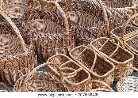 Several rows of wicker baskets. Baskets are woven from vines. The weaving pattern and design. Baskets with handles and lids of different shapes. Oval rectangular and round.