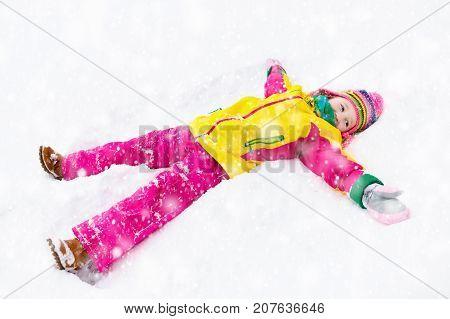 Child Making Snow Angel. Kids Play In Winter Park.