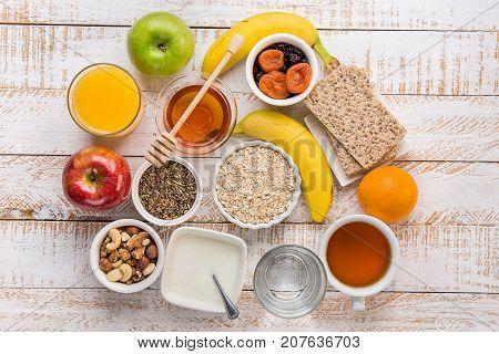 Healthy Food Fiber Source Breakfast Oatmeal Honey Fruits Apples Banana Orange Juice Water Green Tea Nuts. White Plank Wood Table. Rustic. Flat Lay Top View.