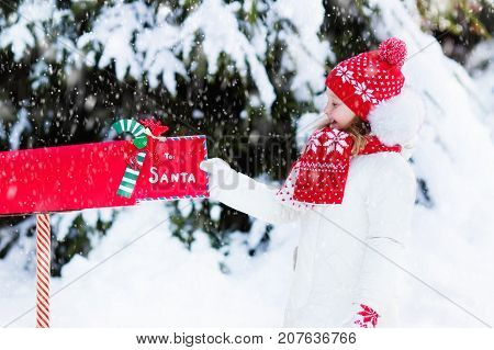 Happy child in knitted reindeer hat and scarf holding letter to Santa with Christmas presents wish list at red mail box in snow under Xmas tree in winter forest. Kids sending post to North Pole.