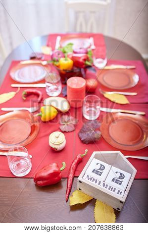 Calendar with date of 22 November on a table served with fancy festive plates on a blurred apartment background. Thanksgiving 2018 celebration.