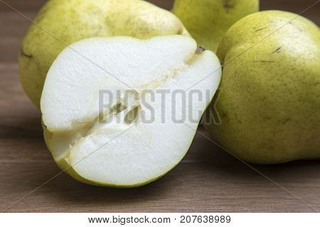 Whole And Sliced Green Pears On Wooden Board