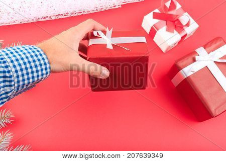 Gift box in human hands. Branch of Christmas tree, ribbons, bow, cones and a ball of brown threads lie on a red background. Cope space. Close-up of gifts.