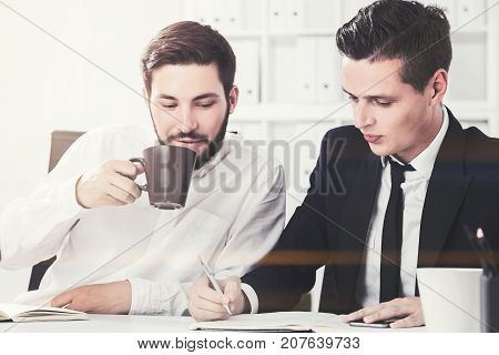 Two young businessmen drinking coffee and discussing their current project in an office. Toned image