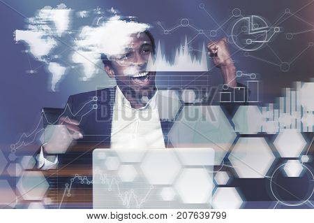 Happy African American businessman is sitting at his laptop in an office and celebrating sealing a good deal. Graphs. Toned image double exposure