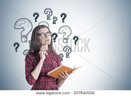 Portrait of a beautiful and pensive young woman wearing a red checkered dress and glasses and holding an open orange book. Gray wall with question marks Mock up