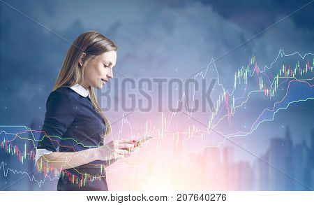 Side view of a young businesswoman with a smartphone standing against a cityscape background with graphs and HUD. Toned image double exposure mock up