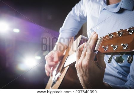 the guitarist is seated playing the guitar