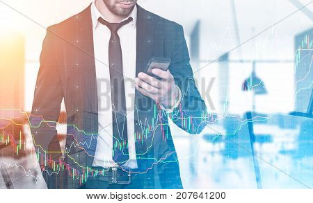 Close up of a young businessman in a suit is looking at his smartphone while standing in an office. A cityscape in the background. Mock up toned image double exposure