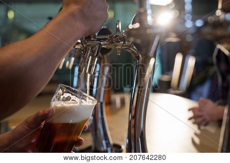 Cropped hands of bartender pouring beer from tap