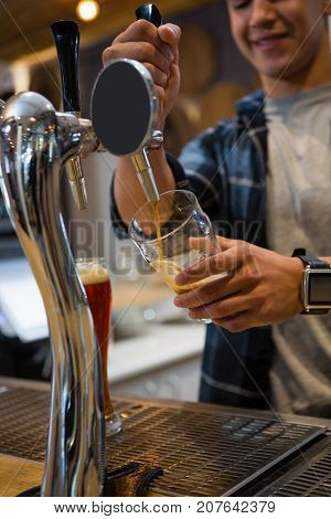 Young bartender pouring drink from tap in glass at restaurant