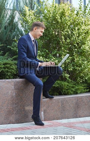 Handsome man outdoors working on computer. Sitting in the park on the nature background. Full lenght of man. Business concept.