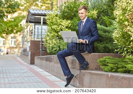 Handsome man in a blue suit outdoors working on computer. Sitting in the park on the nature background. Full lenght of man. Business concept.