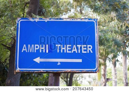 Amphitheater signboard on display in wood and trees
