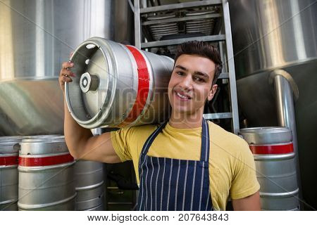 Portrait of smiling male worker carrying keg by storage tanks at brewery