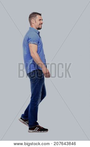 side view of a smiling casual man walking , on white background