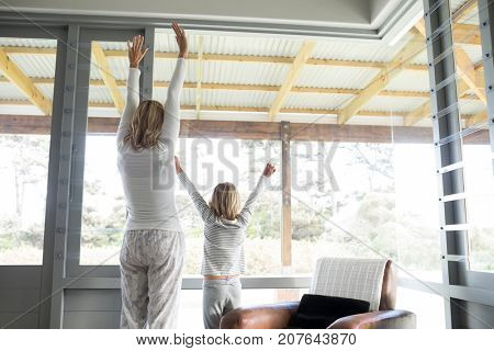 Rear view of mother and son standing with arms up at home