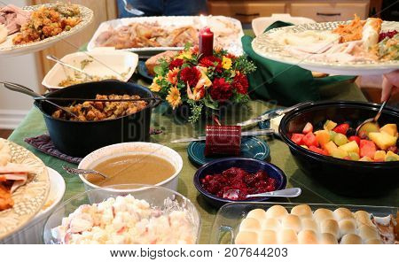 Casual Thanksgiving Feast on Table with Plates Being Filled