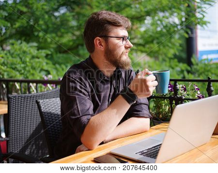 Handsome man outdoors working on computer. Drinking coffe in the cafe on the nature background. Close-up of business man. Business concept.