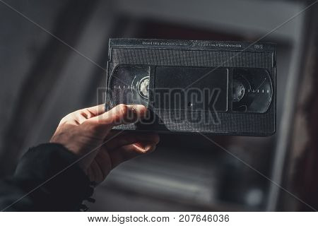 Hand Holds An Old Vhs Cassette. In The Attic.