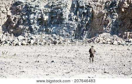 Location shot of soldier in field uniforms with rifle moving in the desert among rocks. Back view