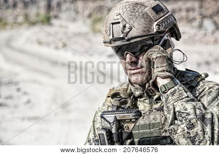 Closeup shot of soldier calliong phone in the desert among rocks