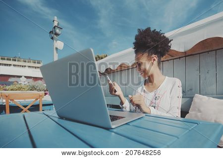 Laughing black girl in cafe outdoors with netbook answering a message on her cell phone; cheerful young biracial lady with curly afro hair holding smartphone and working on laptop in street bar