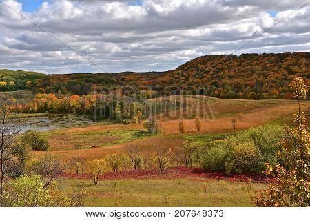 An array of brilliant autumn colors over a countryside of a pond, woods, and hills
