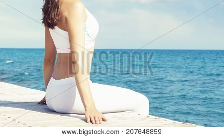 Woman in white sportswear doing yoga on a wooden pier.  Sea and sky background. Yoga, sport, vacation and traveling concept.