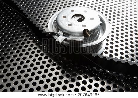 Bearing tensioner and timing belt on a metal surface. Photo from the vignetting effect
