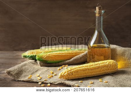 Glass bottle with corn oil on sackcloth fabric