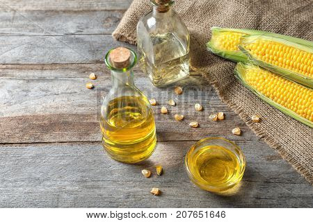 Glassware with corn oil on wooden background