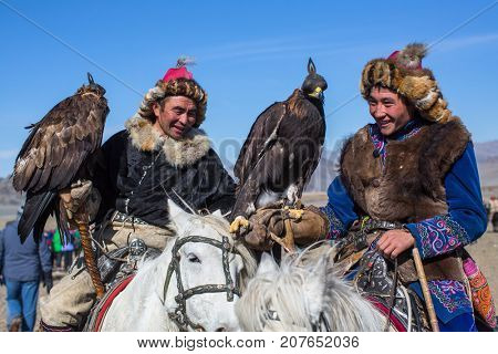 OLGIY, MONGOLIA - SEP 30, 2017: Kazakh Eagle Hunters traditional clothing, with a golden eagles during annual national competition with birds of prey