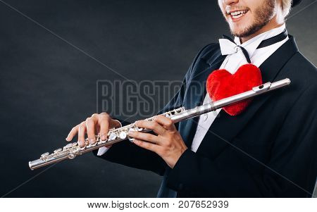 Valentines day love melody concept. Flute music playing male flutist musician performer. Young elegant stylish guy with instrument and red heart