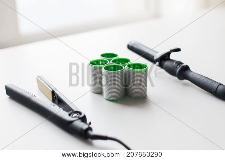 hair tools, beauty and hairdressing concept - curling iron, hot styler and curlers on white background