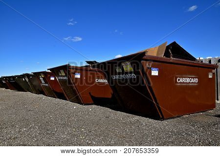 Dumpsters for collecting cardboard and recyclables stand in a row at at depository collection site.