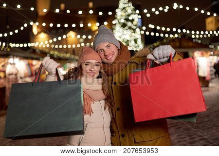 holidays, christmas and people concept - happy couple at with shopping bags in winter