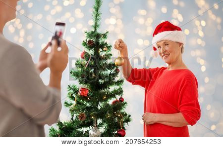 holidays and people concept - happy senior woman decorating christmas tree and posing for photo over lights background