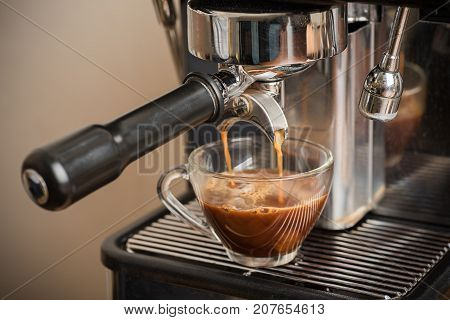Fresh coffee flowing into a cup from espresso machine