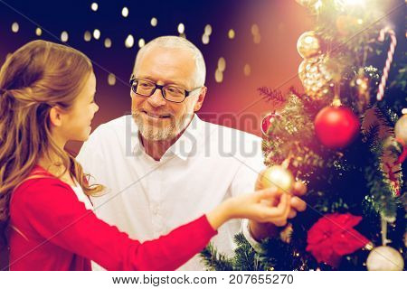 holidays, family and people concept - happy grandfather and granddaughter decorating christmas tree over lights background