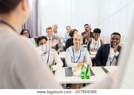 business and education concept - businesswoman or lecturer talking to group of people at conference, presentation or lecture