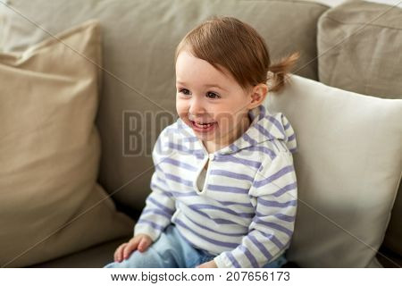childhood, emotions and people concept - happy smiling baby girl sitting on sofa at home