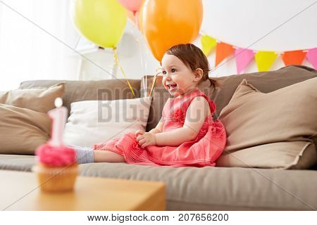 childhood, holidays and people concept - happy baby girl air balloons and garland on birthday party at home