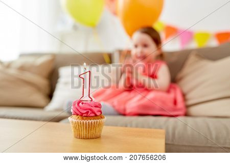 childhood and celebration concept - birthday cupcake with candle for one year old baby girl anniversary at home party