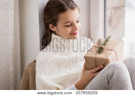 childhood, holidays and people concept - happy beautiful girl with christmas gift sitting at home