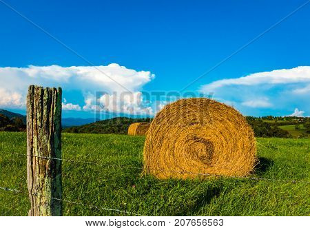 Rustic fence post round bales of hay green grass, blue sky, mountains