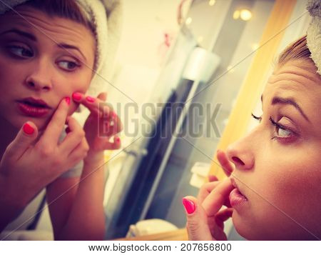 Woman Looking In Mirror Dealing With Acne